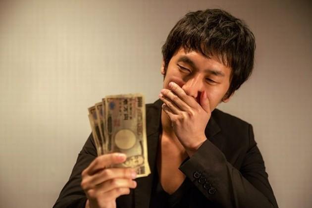 お金を見てほくそ笑む男性